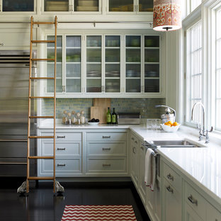 Inspiration for a transitional dark wood floor kitchen remodel in New York with a farmhouse sink, recessed-panel cabinets, white cabinets, blue backsplash, subway tile backsplash and stainless steel appliances
