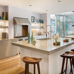 Idéer för funkis kök med öppen planlösning, med en undermonterad diskho, släta luckor, skåp i rostfritt stål, rostfria vitvaror, mellanmörkt trägolv, en köksö och bänkskiva i betong