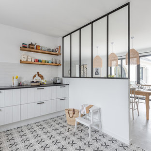 This is an example of a mid-sized beach style u-shaped eat-in kitchen with louvered cabinets, light wood cabinets, quartz benchtops, white splashback, ceramic splashback, stainless steel appliances, cement tiles, grey floor, an integrated sink, no island and black benchtop.