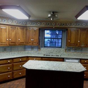 ダラスの大きいモダンスタイルのおしゃれなキッチン (ダブルシンク、レイズドパネル扉のキャビネット、中間色木目調キャビネット、御影石カウンター、白いキッチンパネル、石スラブのキッチンパネル、シルバーの調理設備の、レンガの床、赤い床) の写真