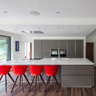 他の地域の中くらいのモダンスタイルのおしゃれなキッチン (ドロップインシンク、フラットパネル扉のキャビネット、グレーのキャビネット、人工大理石カウンター、パネルと同色の調理設備、セラミックタイルの床、茶色い床、白いキッチンカウンター) の写真