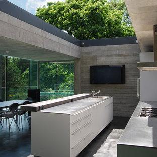 Foto på ett mellanstort funkis kök, med en köksö, släta luckor, vita skåp, bänkskiva i rostfritt stål och en nedsänkt diskho