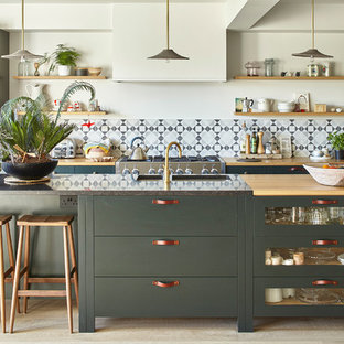 This is an example of a transitional galley kitchen in Sussex with a double-bowl sink, shaker cabinets, green cabinets, wood benchtops, grey splashback, mosaic tile splashback, light hardwood floors, with island and beige floor.