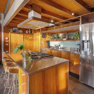 Kolonialstil Küche mit integriertem Waschbecken, flächenbündigen Schrankfronten, hellbraunen Holzschränken, Edelstahl-Arbeitsplatte, Küchengeräten aus Edelstahl, Kücheninsel und grauem Boden in Sydney