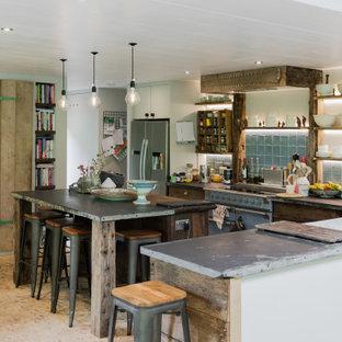 ハンプシャーのインダストリアルスタイルのおしゃれなキッチン (エプロンフロントシンク、フラットパネル扉のキャビネット、中間色木目調キャビネット、青いキッチンパネル、カラー調理設備、ベージュの床、グレーのキッチンカウンター) の写真