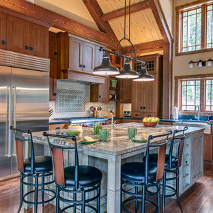 This is an example of a large arts and crafts l-shaped kitchen in Nashville with a farmhouse sink, shaker cabinets, medium wood cabinets, granite benchtops, grey splashback, matchstick tile splashback, stainless steel appliances, medium hardwood floors, with island, brown floor and multi-coloured benchtop.
