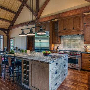 ナッシュビルの大きいトラディショナルスタイルのおしゃれなキッチン (エプロンフロントシンク、シェーカースタイル扉のキャビネット、中間色木目調キャビネット、御影石カウンター、グレーのキッチンパネル、ボーダータイルのキッチンパネル、シルバーの調理設備、無垢フローリング、茶色い床、マルチカラーのキッチンカウンター) の写真
