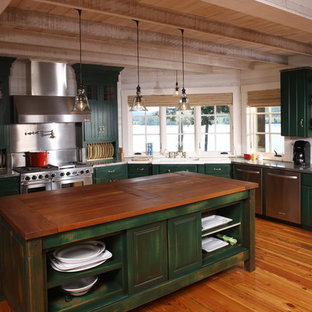 This is an example of a large country u-shaped separate kitchen in Other with an undermount sink, louvered cabinets, green cabinets, wood benchtops, beige splashback, stainless steel appliances, dark hardwood floors and with island.