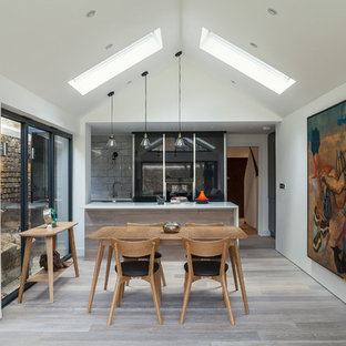 Contemporary kitchen/diner in London with light hardwood flooring and a breakfast bar.