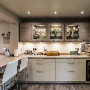 Идея дизайна: отдельная, п-образная кухня среднего размера в современном стиле с врезной раковиной, плоскими фасадами, бежевыми фасадами, столешницей из кварцита, бежевым фартуком, черной техникой и полуостровом