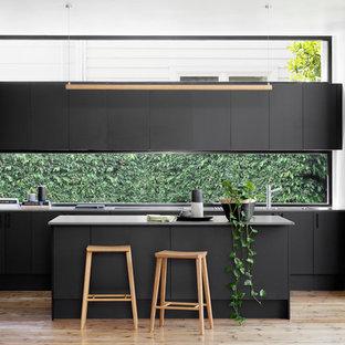 Ejemplo de cocina en L, contemporánea, de tamaño medio, abierta, con fregadero encastrado, armarios con paneles lisos, puertas de armario negras, encimera de cuarzo compacto, salpicadero de vidrio, electrodomésticos de acero inoxidable, suelo de madera clara, una isla y suelo beige