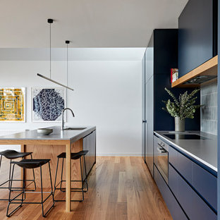 Photo of a large modern galley eat-in kitchen in Melbourne with a double-bowl sink, flat-panel cabinets, blue cabinets, quartz benchtops, grey splashback, ceramic splashback, black appliances, with island, grey benchtop, medium hardwood floors and brown floor.
