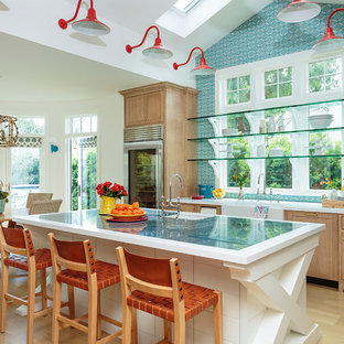 Новые идеи обустройства дома: огромная п-образная кухня в морском стиле с раковиной в стиле кантри, фасадами в стиле шейкер, светлыми деревянными фасадами, мраморной столешницей, синим фартуком, фартуком из цементной плитки, техникой из нержавеющей стали, светлым паркетным полом, островом, синей столешницей, коричневым полом и обеденным столом