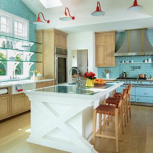ロサンゼルスの巨大なビーチスタイルのおしゃれなキッチン (エプロンフロントシンク、シェーカースタイル扉のキャビネット、大理石カウンター、青いキッチンパネル、セメントタイルのキッチンパネル、茶色い床、中間色木目調キャビネット、カラー調理設備、無垢フローリング、白いキッチンカウンター) の写真