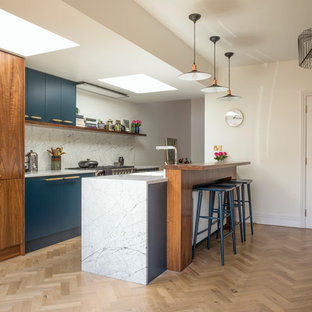 Design ideas for a medium sized contemporary galley kitchen/diner in London with a submerged sink, flat-panel cabinets, white splashback, light hardwood flooring, a breakfast bar and beige floors.