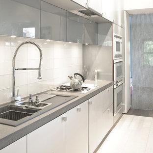 Esempio di una cucina contemporanea di medie dimensioni con lavello da incasso, ante lisce, ante bianche, top alla veneziana, paraspruzzi bianco, paraspruzzi con piastrelle di vetro, elettrodomestici in acciaio inossidabile, pavimento in pietra calcarea e isola