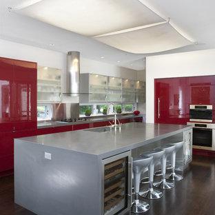 ワシントンD.C.の広いトランジショナルスタイルのおしゃれなキッチン (シルバーの調理設備、フラットパネル扉のキャビネット、赤いキャビネット、コンクリートカウンター、アンダーカウンターシンク、濃色無垢フローリング、グレーのキッチンカウンター) の写真