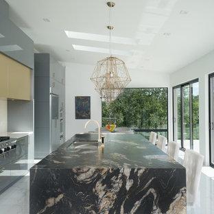 Aménagement d'une cuisine contemporaine avec un évier encastré, un placard à porte plane, des portes de placard grises, un électroménager en acier inoxydable et un îlot central.