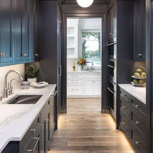 Inspiration pour une arrière-cuisine parallèle marine avec un évier encastré, un placard à porte shaker, des portes de placard noires, un sol en bois brun et un plan de travail blanc.