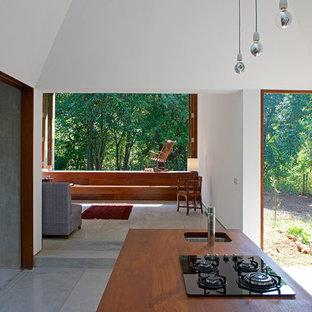 Ejemplo de cocina minimalista, de tamaño medio, con fregadero bajoencimera, encimera de madera, electrodomésticos negros, suelo de terrazo y una isla