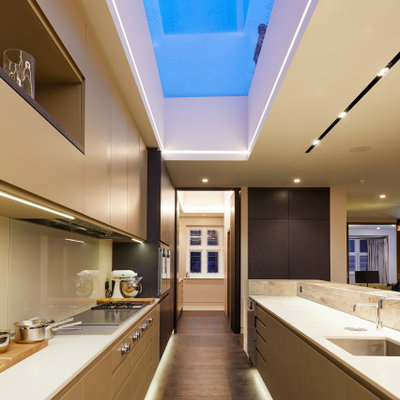 Example of a large trendy galley dark wood floor and brown floor kitchen design in London with an undermount sink, flat-panel cabinets, solid surface countertops, beige backsplash, glass tile backsplash, paneled appliances, white countertops, beige cabinets and no island