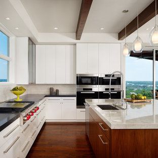 Example of a trendy galley dark wood floor open concept kitchen design in Austin with a single-bowl sink, flat-panel cabinets, white cabinets, white backsplash, stainless steel appliances and an island