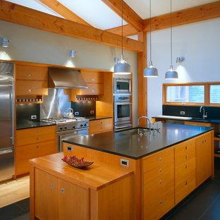 Inspiration för ett stort funkis kök, med en undermonterad diskho, släta luckor, skåp i mellenmörkt trä, svart stänkskydd, stänkskydd i sten, rostfria vitvaror, granitbänkskiva, skiffergolv, en köksö och svart golv