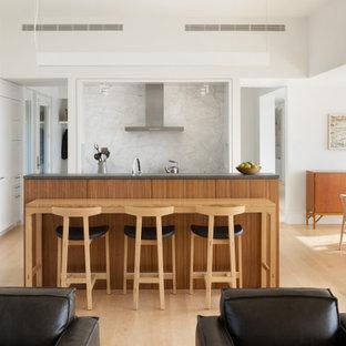 Réalisation d'une cuisine ouverte linéaire design avec un placard à porte affleurante, des portes de placard blanches, une crédence en quartz modifié, un électroménager noir, un îlot central et un plan de travail gris.