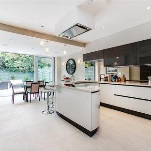 Cette photo montre une cuisine américaine tendance en U avec un placard à porte plane, des portes de placard blanches, une crédence en carreau de miroir et un sol beige.