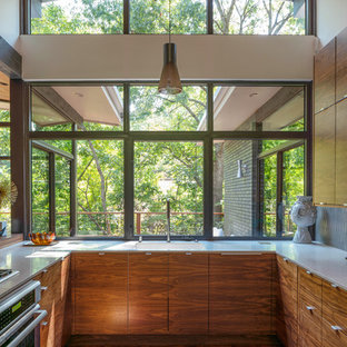 Small mid-century modern kitchen ideas - Kitchen - small mid-century modern u-shaped medium tone wood floor kitchen idea in Dallas with a single-bowl sink, flat-panel cabinets, medium tone wood cabinets, quartz countertops, white countertops, window backsplash and stainless steel appliances