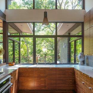 Exempel på ett litet retro vit vitt u-kök, med en enkel diskho, släta luckor, skåp i mellenmörkt trä, bänkskiva i kvarts, fönster som stänkskydd, rostfria vitvaror och mellanmörkt trägolv