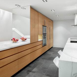 Foto de cocina de galera, contemporánea, de tamaño medio, abierta, con armarios con paneles lisos, puertas de armario de madera oscura, electrodomésticos de acero inoxidable, una isla, fregadero bajoencimera, encimera de mármol, suelo de pizarra y suelo gris