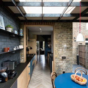 Photo of an industrial galley kitchen in London with a submerged sink, flat-panel cabinets, light wood cabinets, black splashback, brick splashback, light hardwood flooring, no island and beige floors.
