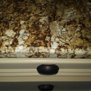 Offene, Mittelgroße Moderne Küche in U-Form mit Einbauwaschbecken, profilierten Schrankfronten, gelben Schränken, Granit-Arbeitsplatte, Küchenrückwand in Beige, Rückwand aus Travertin, schwarzen Elektrogeräten, braunem Holzboden, Kücheninsel und braunem Boden in Houston