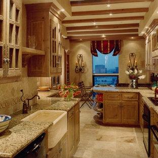 Идея дизайна: параллельная кухня среднего размера в классическом стиле с обеденным столом, полуостровом, фасадами с выступающей филенкой, светлыми деревянными фасадами, столешницей из гранита, бежевым фартуком, фартуком из каменной плитки, черной техникой, раковиной в стиле кантри и полом из травертина