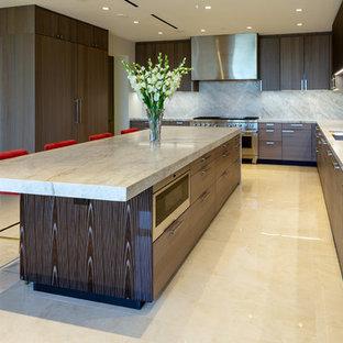 Cette image montre une très grand cuisine ouverte design avec un évier 3 bacs, un placard à porte plane, des portes de placard grises, un plan de travail en quartz, une crédence beige, une crédence en dalle de pierre, un électroménager en acier inoxydable, un sol en carrelage de porcelaine, un sol beige et un plan de travail beige.