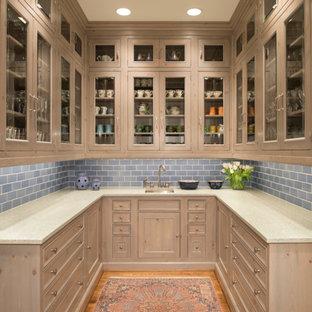 Kleine Klassische Küche ohne Insel in U-Form mit Vorratsschrank, Glasfronten, hellen Holzschränken, Küchenrückwand in Blau, braunem Holzboden, Marmor-Arbeitsplatte und Rückwand aus Keramikfliesen in Houston