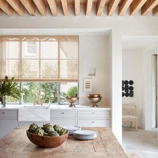 Идея дизайна: большая угловая кухня в стиле современная классика с обеденным столом, раковиной в стиле кантри, плоскими фасадами, серыми фасадами, серым полом, белой столешницей и деревянным потолком
