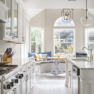 Traditional eat-in kitchen pictures - Elegant galley light wood floor and gray floor eat-in kitchen photo in Houston with an undermount sink, raised-panel cabinets, white cabinets, white backsplash, subway tile backsplash, stainless steel appliances, an island and white countertops