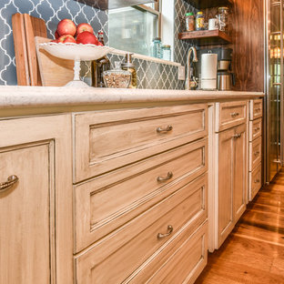 Inspiration for a transitional single-wall eat-in kitchen in Houston with a drop-in sink, recessed-panel cabinets, beige cabinets, marble benchtops, blue splashback, glass tile splashback, stainless steel appliances, light hardwood floors, with island and beige floor.