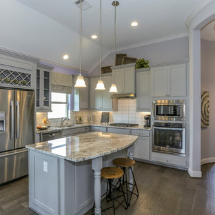Photo of a mid-sized l-shaped eat-in kitchen in Houston with a double-bowl sink, recessed-panel cabinets, grey cabinets, granite benchtops, white splashback, subway tile splashback, stainless steel appliances, dark hardwood floors, with island and purple floor.