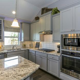Mittelgroße Wohnküche in L-Form mit Doppelwaschbecken, Schrankfronten mit vertiefter Füllung, grauen Schränken, Granit-Arbeitsplatte, Küchenrückwand in Weiß, Rückwand aus Metrofliesen, Küchengeräten aus Edelstahl, dunklem Holzboden, Kücheninsel und lila Boden in Houston