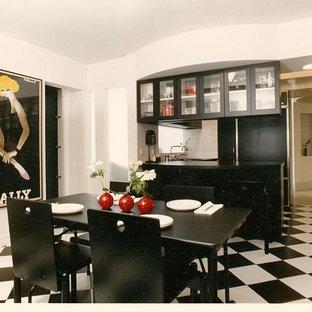 Expansive modern u-shaped open plan kitchen in New York with a single-bowl sink, flat-panel cabinets, black cabinets, laminate benchtops, black splashback, cement tile splashback, black appliances and ceramic floors.