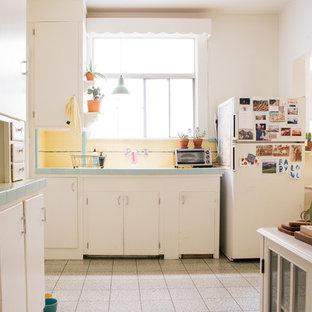 サンフランシスコの小さいエクレクティックスタイルのおしゃれなキッチン (タイルカウンター、白い調理設備、リノリウムの床、フラットパネル扉のキャビネット、白いキャビネット、黄色いキッチンパネル) の写真