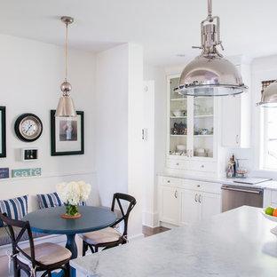 Idées déco pour une grande cuisine américaine romantique en L avec un sol en bois brun, un évier encastré, un placard à porte shaker, des portes de placard blanches, un plan de travail en marbre, un électroménager en acier inoxydable et un îlot central.