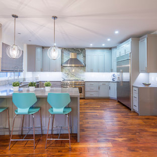 Transitional kitchen ideas - Transitional u-shaped medium tone wood floor kitchen photo in Los Angeles with an undermount sink, beaded inset cabinets, gray cabinets, gray backsplash, subway tile backsplash, stainless steel appliances and no island