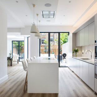 This is an example of a medium sized classic kitchen/diner in London with a submerged sink, flat-panel cabinets, white cabinets, quartz worktops, stainless steel appliances, light hardwood flooring, an island, beige floors and white worktops.