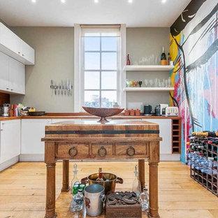Große, Geschlossene Eklektische Küche in L-Form mit flächenbündigen Schrankfronten, weißen Schränken, Arbeitsplatte aus Holz, Küchenrückwand in Braun, Rückwand aus Holz, Küchengeräten aus Edelstahl, braunem Holzboden, Kücheninsel und gelbem Boden in London