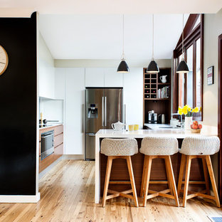 Mid-sized trendy u-shaped medium tone wood floor kitchen photo in Sydney with an undermount sink, flat-panel cabinets, white cabinets and stainless steel appliances
