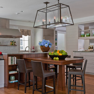 Example of a trendy eat-in kitchen design in Boston with stainless steel appliances, stone tile backsplash, white cabinets and white backsplash